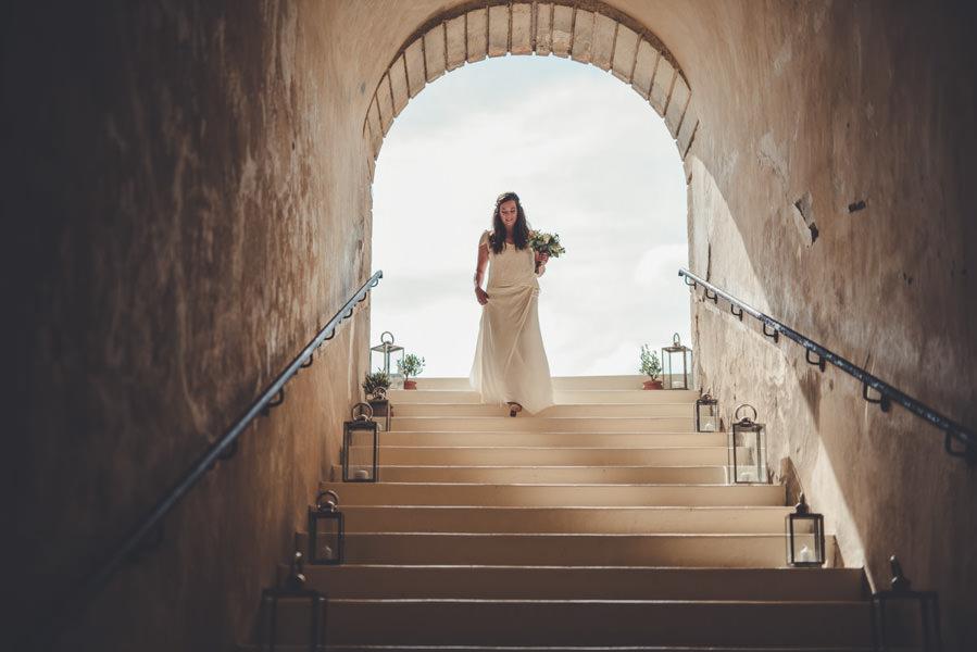 la mariée qui descend l'escalier devant la cérémonie au chateau