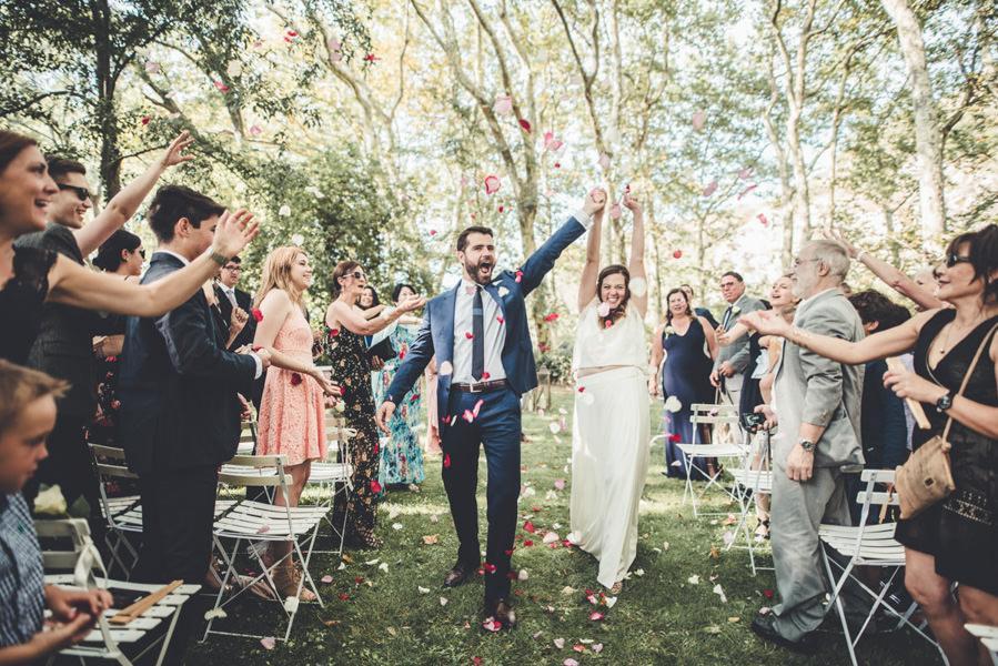 les mariés partent sous les lancers de pétales de fleurs après la cérémonie dans le jardin à Saint-Jean-d'Illac