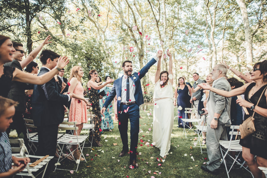 les mariés hurlent de joie sous les lancers de fleurs après la fin de la cérémonie